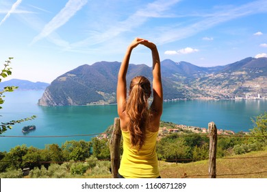 Excited attractive young woman in sportswear stretching enjoying Lake Iseo landscape in the morning, North Italy. Cheerful mood, true emotions, healthy lifestyle.