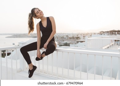 Excited attractive young woman in sportswear enjoying sunrise on seafront in the morning in tropical country. Cheerful mood, true emotions, healthy lifestyle, smiling with closed eyes
