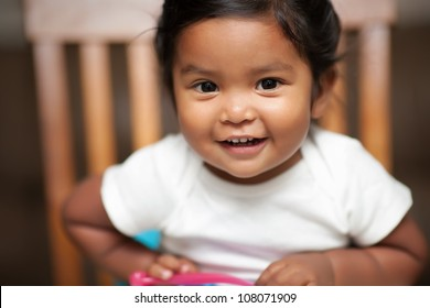 excited baby girl holding a spoon and sitting on a booster seat
