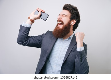 Excited bearded businessman wearing airpods, listening music, sing and dance ove gray background