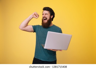 Excited bearded guy holding a laptop while celebrating with rised arm, over yellow background