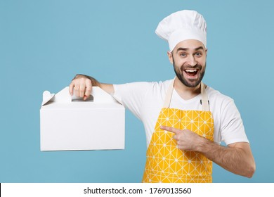 Excited bearded male chef or cook baker man in apron white t-shirt toque chefs hat isolated on blue background. Cooking food concept. Pointing index finger on cake dessert in unmarked cardboard box