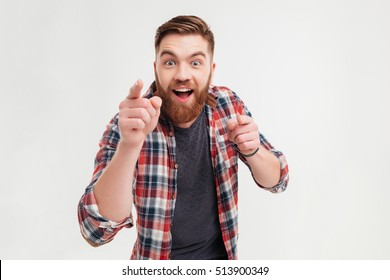 Excited bearded man in checkered shirt pointing fingers at camera isolated on a white background