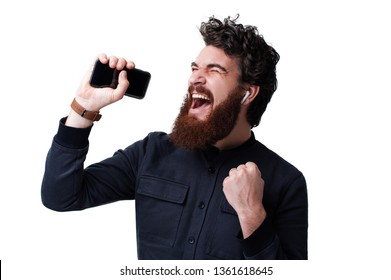 Excited bearded man holding mobile, wearing airpods, listening music, sing and dance over white background