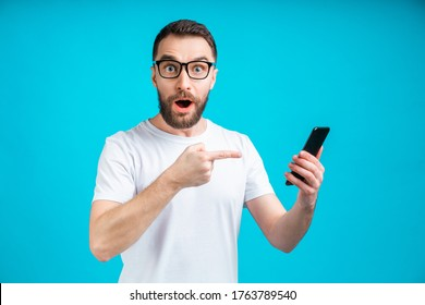 Excited bearded man in trendy eyeglasses pointing at his smartphone touchscreen with index finger surprised with great news he just got with a message.