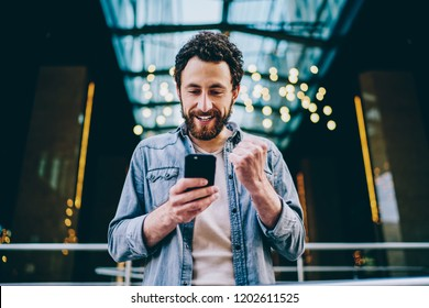 Excited bearded young man blogger cheering favourite team during live stream on website on modern smartphone.Cheerful hipster guy celebrating victory in internet contest on web page holding cellular