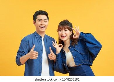Excited beautiful asian couple shows thumb up gesture agree to do something and collaborate against orange wall, did great job, show approval, like idea. Everything will be OK.