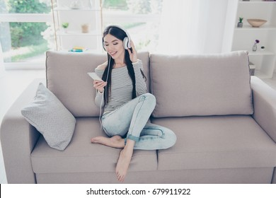 Excited beautiful asian teen is listening to music in big white earphones on her pda at home. She is wearing casual clothes, sitting on cozy beige couch