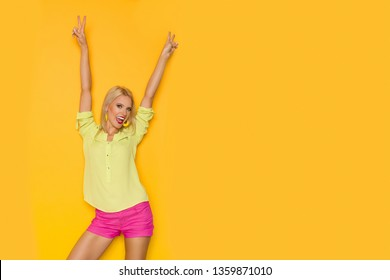 Excited beautiful blond woman in yellow shirt and pink shorts is standing with arms raised and shouting. Three quarter length studio shot on yellow background.