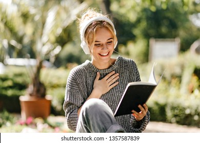 Excited beautiful girl reads her notes in warm autumn day. Outdoor photo of glad charming woman with book