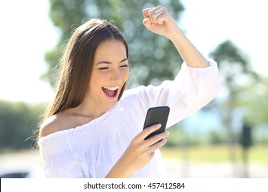 Excited beautiful girl receiving a sms message with good news in a mobile phone outside in a park with a green background