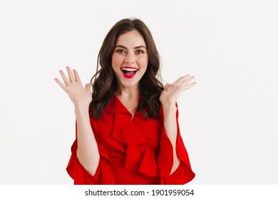 Aufgeregt schönes Mädchen mit rotem Kleid, das auf der Kamera einzeln auf weißem Hintergrund steht