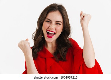Excited beautiful girl wearing red dress making winner gesture isolated over white background