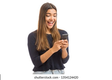 Excited beautiful woman receiving SMS in mobile phone over plain background
