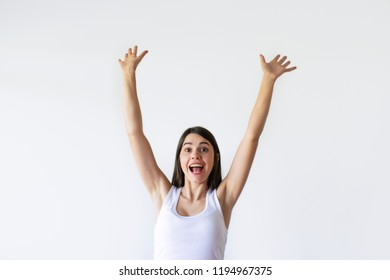 Excited beautiful woman yelling and celebrating with hands up. Attractive happy girl triumphing and looking at camera. Isolated on white. Triumph concept