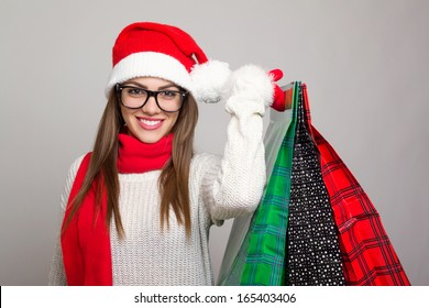 Excited beautiful young Caucasian brunette woman shopping for Christmas wearing Santa hat and eye glasses holding colorful shopping bags against dark gray background.