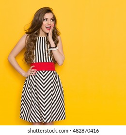 Excited beautiful young woman in black and white striped dress posing with hand on hip, looking away, holding hand on chin and shouting. Three quarter length studio shot on yellow background.