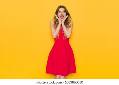 Excited beautiful young woman in red dress is holding head in hands, looking at camera and shouting. Three quarter length studio shot on yellow background.