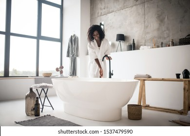 Excited before bath. Curly beautiful woman feeling excited before having foamy bath in light spacious bathroom