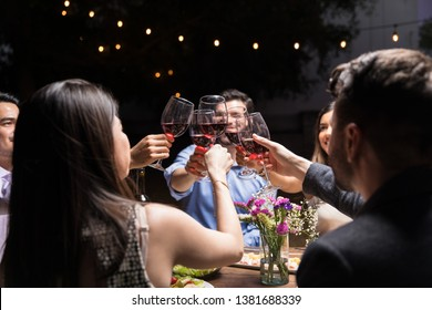 Excited best friends clinking red wine glasses at backyard party during weekend