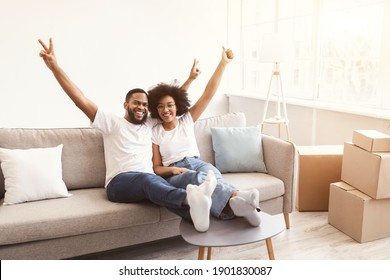 Excited Black Family Couple Celebrating Moving New House After Real Estate Purchase And Relocation Sitting Indoors, Smiling To Camera. Apartment Rent And Ownership Concept, Copy Space