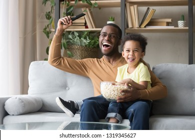 Excited black father with toddler son fans watching football sport tv game celebrating goal, happy african dad and little kid child cheering favorite soccer team victory at home sitting on couch
