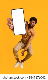 Excited black guy holding smartphone, showing blank screen, jumping up over orange studio background. Handsome african american young man recommending new mobile application, collage