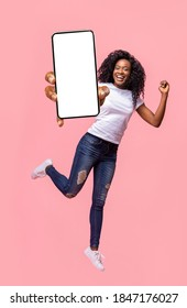 Excited black lady holding smartphone, showing blank screen, jumping up over pink studio background. Attractive african american young woman recommending new mobile application, collage
