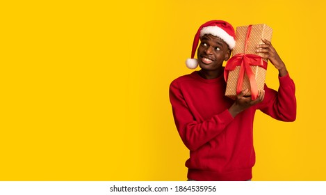 Excited Black Man In Santa Hat Shaking Wrapped Gift Box, Wonder What's Inside, Receiving Christmas Presents While Standing Over Yellow Background, Enjoying Celebrating Winter Xmas Holidays, Copy Space
