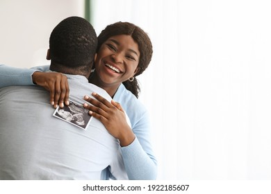 Excited black woman holding ultrasound image and hugging her man, copy space. Happy african american couple future parents embracing, got good news about pregnancy, home interior
