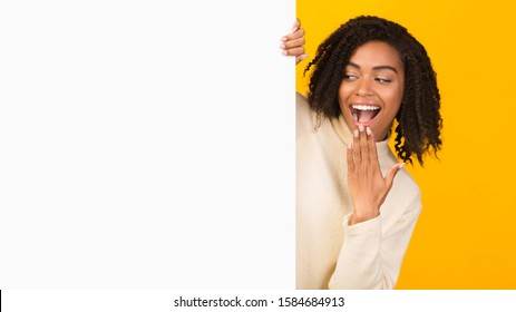 Excited Black Woman Looking Over Copy Space, Hiding Behind Blank Billboard, Peeking Out White Placard