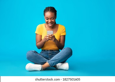 Excited Black Woman With Smartphone Using Mobile Phone Application Sitting Over Blue Studio Background. Texting, Communication, Cellphone App Concept. Free Space For Text