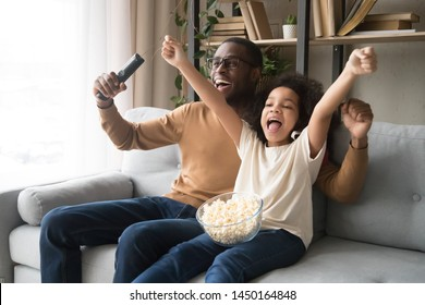 Excited black young dad and preschooler daughter eat popcorn watching football match together, happy african American father and girl child relax on couch cheering team enjoy game on TV at home