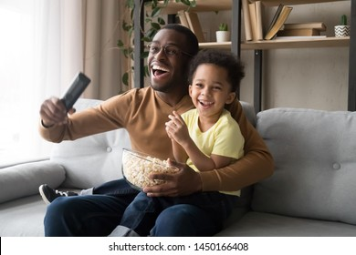 Excited black young father and preschooler son sit on couch eating popcorn enjoy football match on TV cheering, smiling overjoyed african American dad and funny boy child fans watch game at home