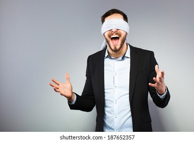 excited blindfolded man in black coat on grey background