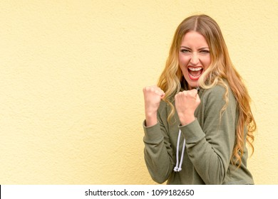 Excited blond woman cheering and clenching her fists as she celebrates a personal victory or success over a yellow studio background with copy space