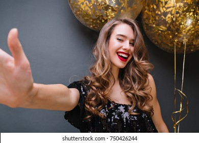 Excited blonde girl with red lips making selfie on dark background during festive. Indoor portrait of glad european female model in black dress posing in front of party balloons.