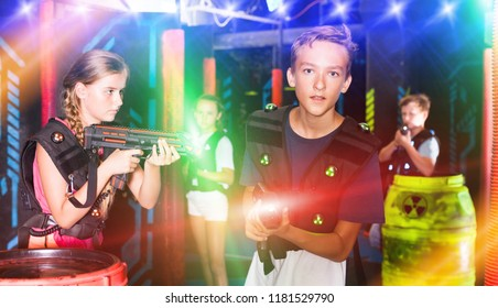 Excited boy aiming laser gun at other players during lasertag game in dark room