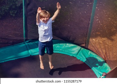 Excited boy bouncing on the trampoline outdoors