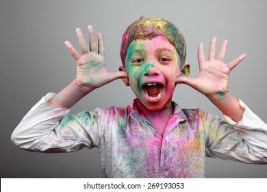 Excited boy with face smeared with colored powder. Concept for festival Holi