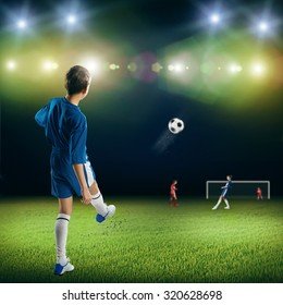 Excited boy football player at stadium kicking ball