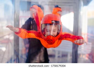 Excited boy in orange helmet flying in aerodynamic tube (wind tunnel). Skydiving training.