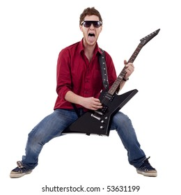 excited boy playing a guitar and sticking his tongue out while playing