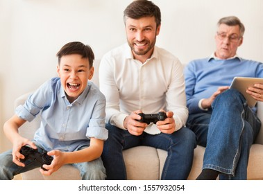 Excited Boy Playing Video Games With Dad And Grandpa Sitting Together On Sofa At Home. Multigenerational Friendship.
