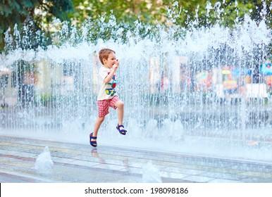 excited boy running between water flow in city park