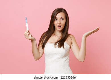 Excited bride woman in wedding dress spreading hands, hold pregnancy test isolated on pastel pink background. Medical healthcare gynecological pregnancy fertility maternity people concept. Copy space