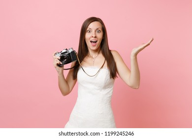 Excited bride woman in white wedding dress spreading hands holding retro vintage photo camera choosing staff, photographer isolated on pink background. Wedding to do list. Organization of celebration