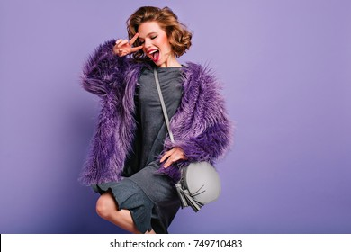Excited brunette girl in gray dress dancing with smile on purple background. Cheerful curly female woman in fur coat enjoying photoshoot and posing with peace sign.