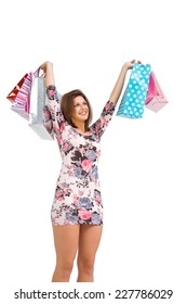 Excited brunette holding up shopping bags on white background