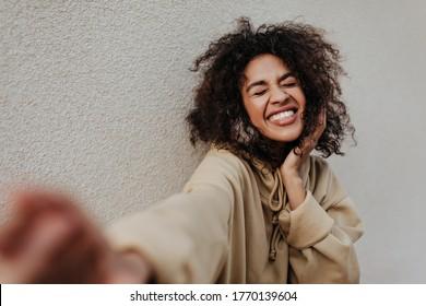 Excited brunette woman in beige hoodie smiles with closed eyes. Dark-skinned girl takes selfie on grey background.